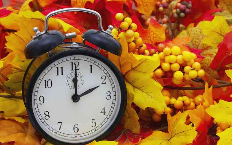 Clock and Autumn leaves, symbolizing the end of Daylight Savings Time.