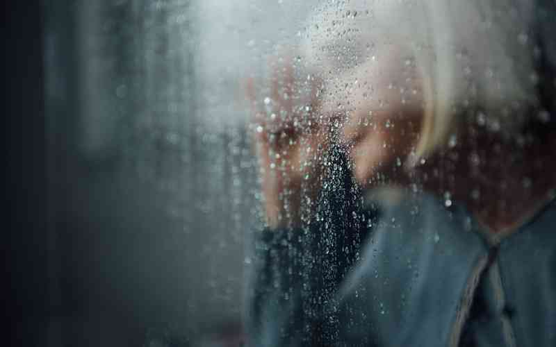 Senior woman behind a window in the rain, symbolizing feelings of loneliness and isolation.